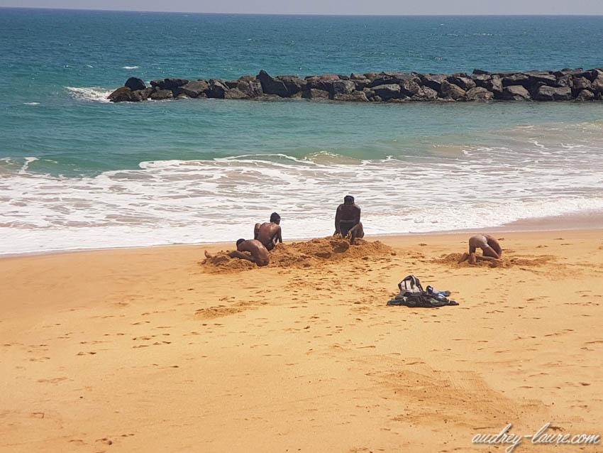 Enfants qui creusent dans le sable sur une plage de Tangalle au Sri Lanka
