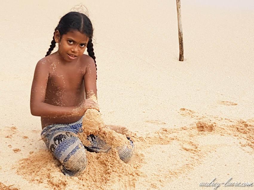 Petite Sri Lankaise jouant dans le sable fin